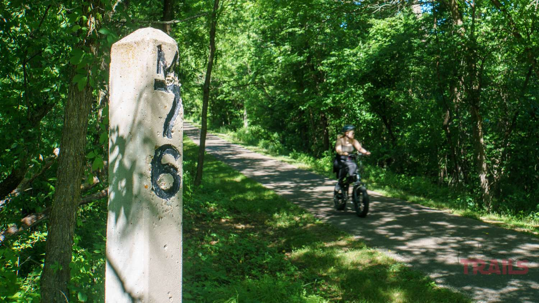 A concrete mile marker post along a bike trail