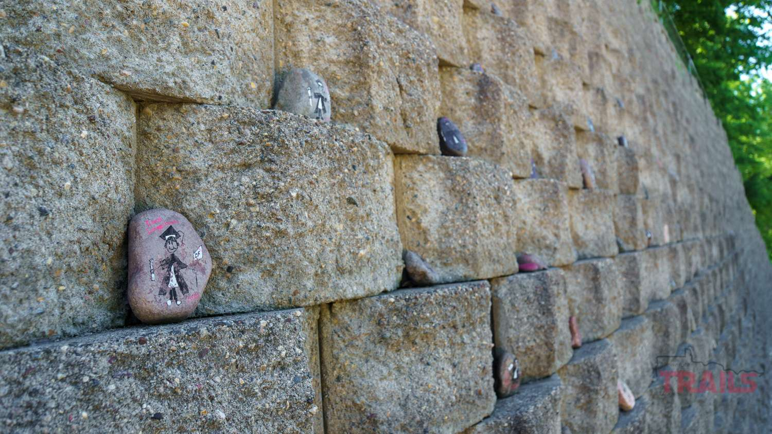 Decoratively handpainted rocks nestled into the cracks of a block wall