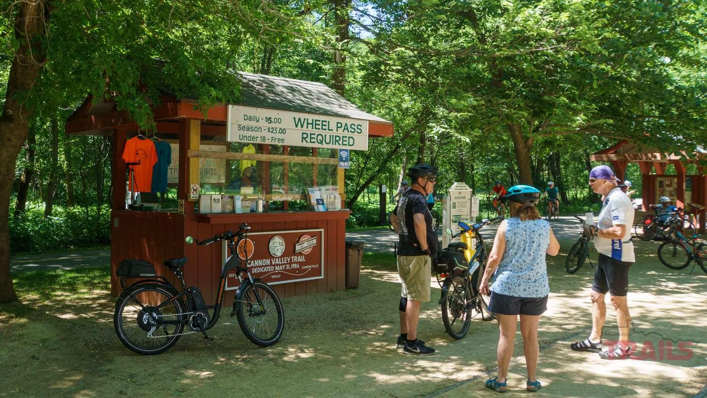 People wearing helmets mill around in front of an info kiosk along a bike trail