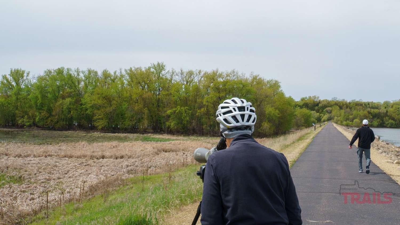 A woman wearing a bike helmet tries to spot a birds nest through a spotting scope