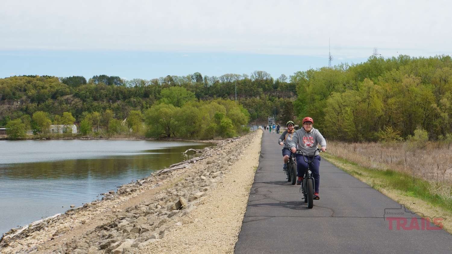 Two people on fat tire biccycles ride along the scenic river dike trail section in Hastings, Mn