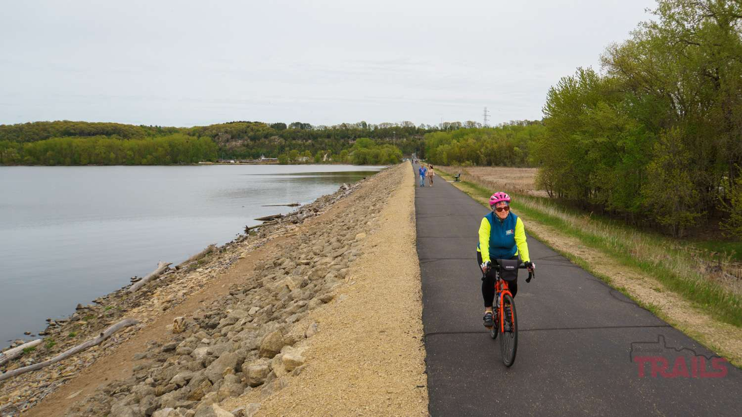 A woman crosses Hastings' river dike trail on a bicycle in the spring