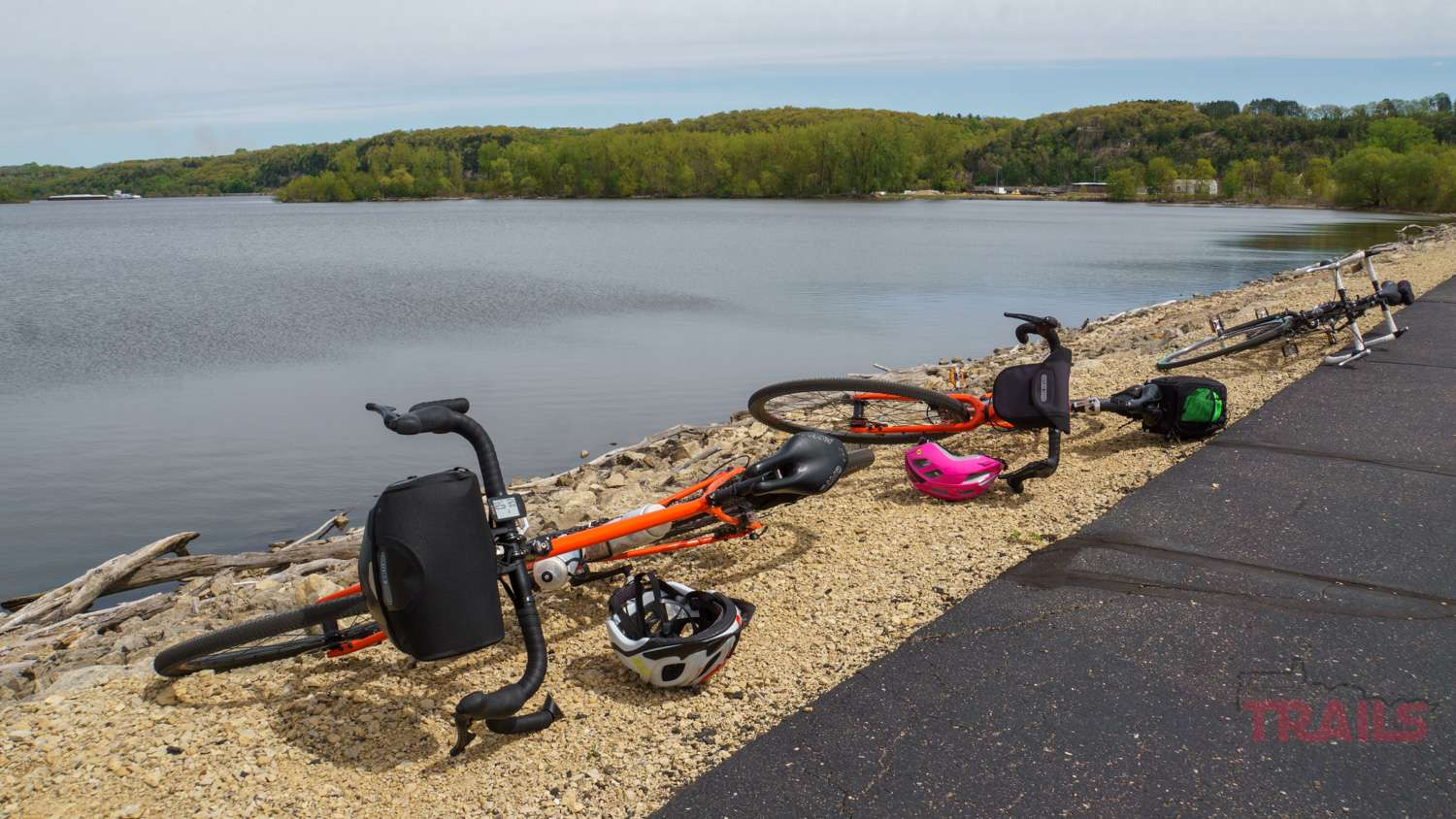 Three bicycles are lying on their sides along a paved trail across a river
