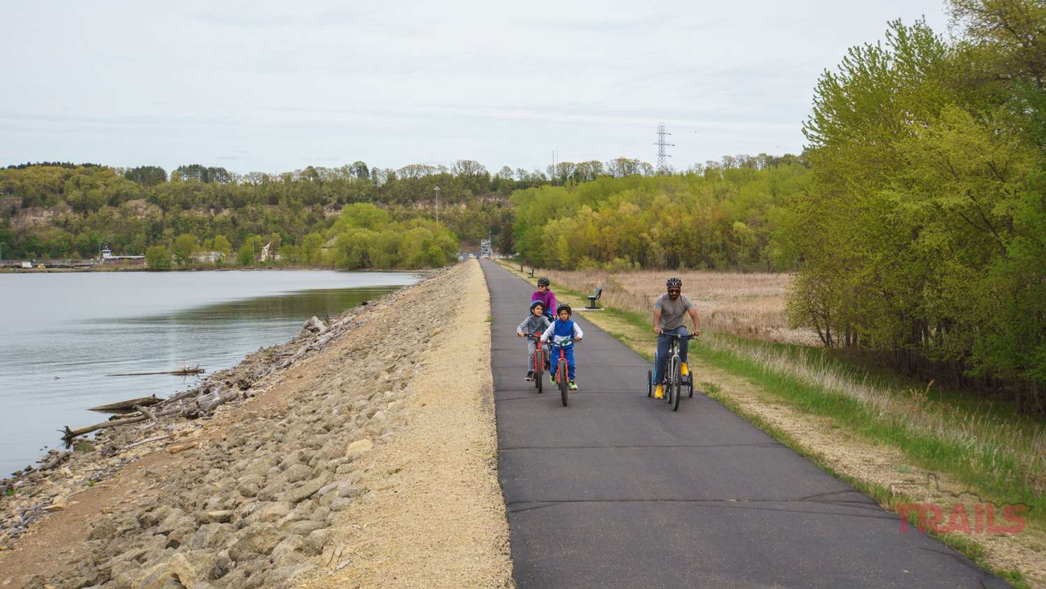 A family of four crosses Hastings' river dike trail on bicycles