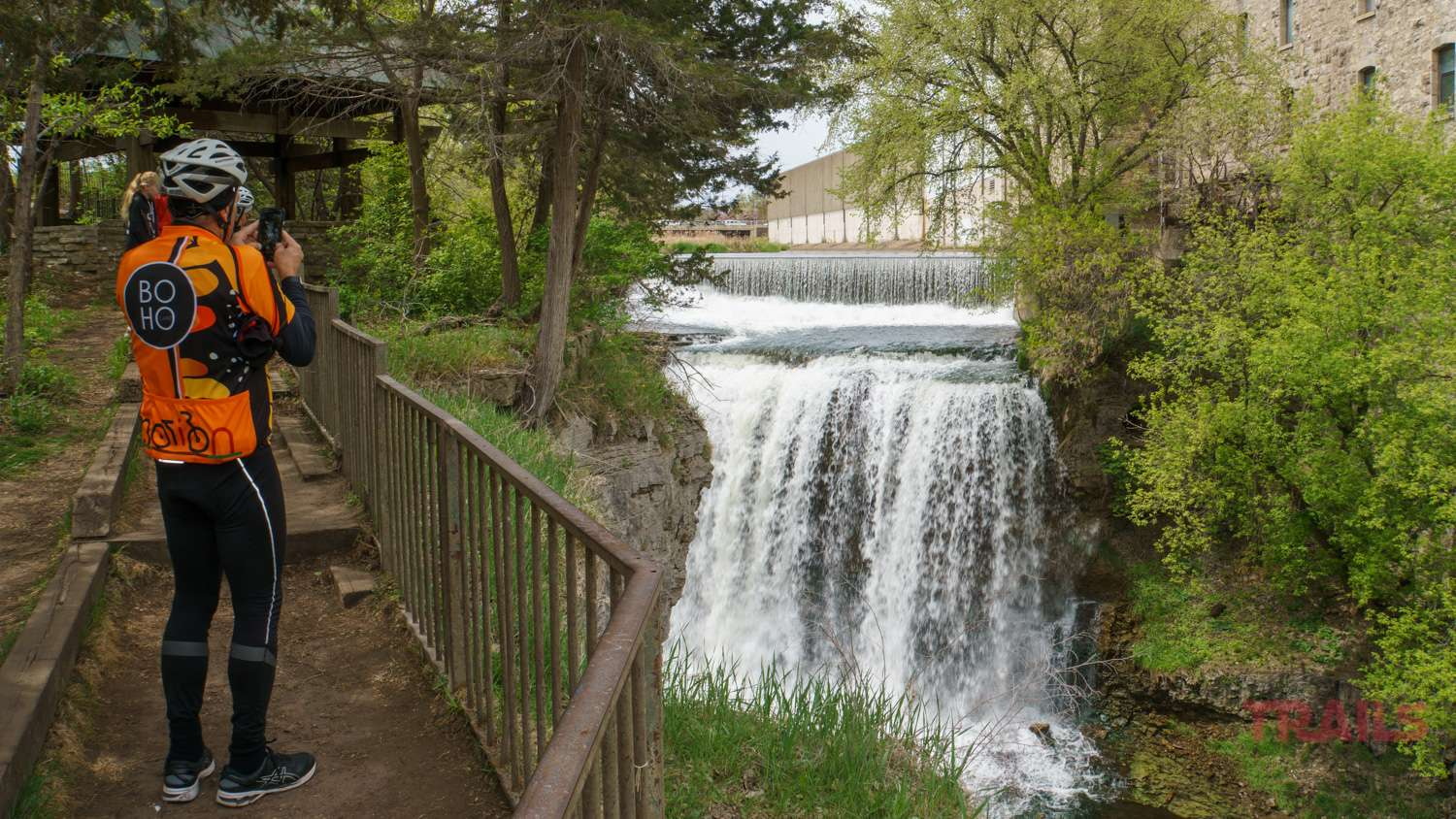 A man in bike gear takes a photo of Vermillion Falls in Hastings, MN