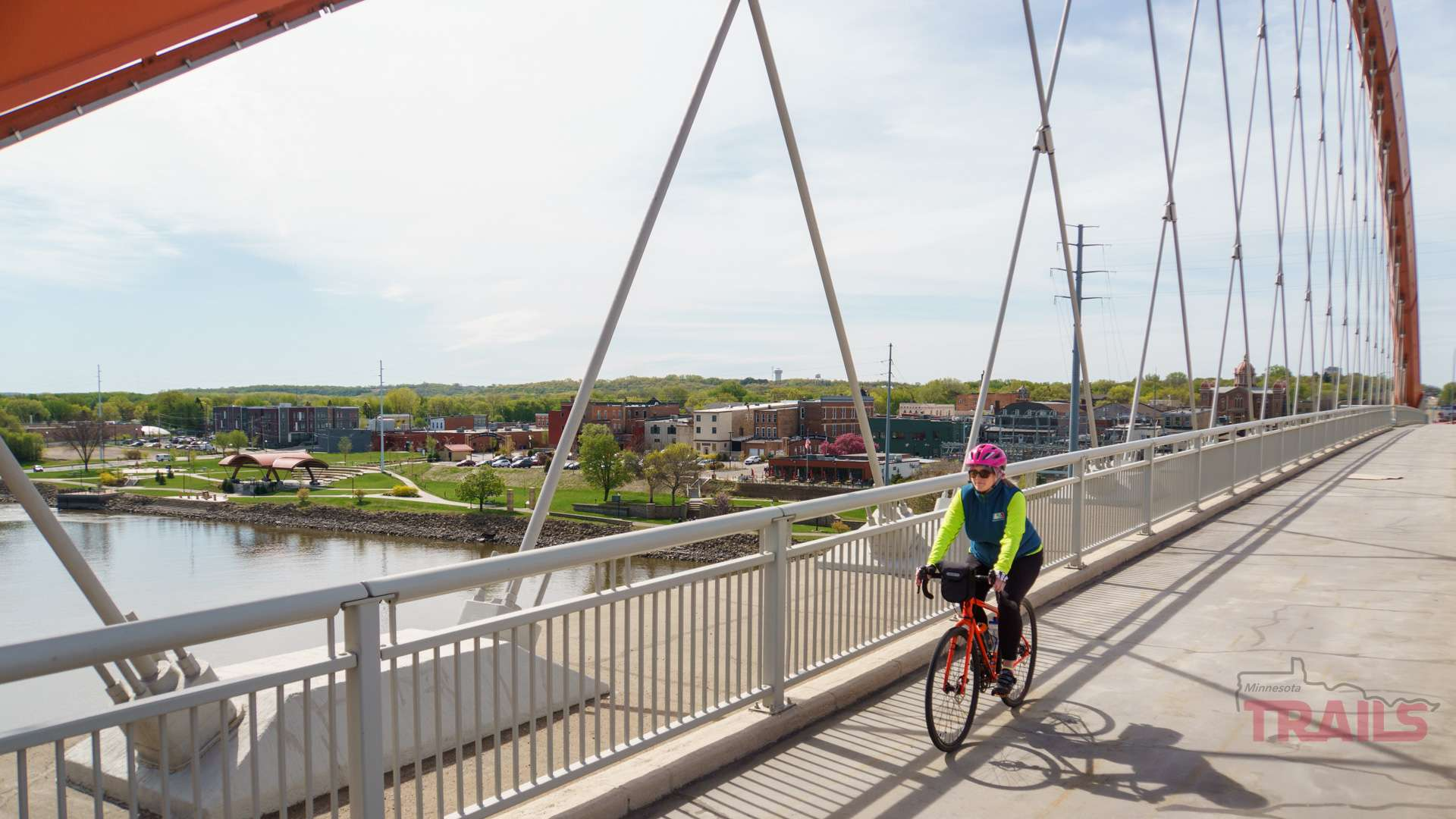A woman crosses Hastings' iconic bridge over the Mississippi on a bicycle in the spring