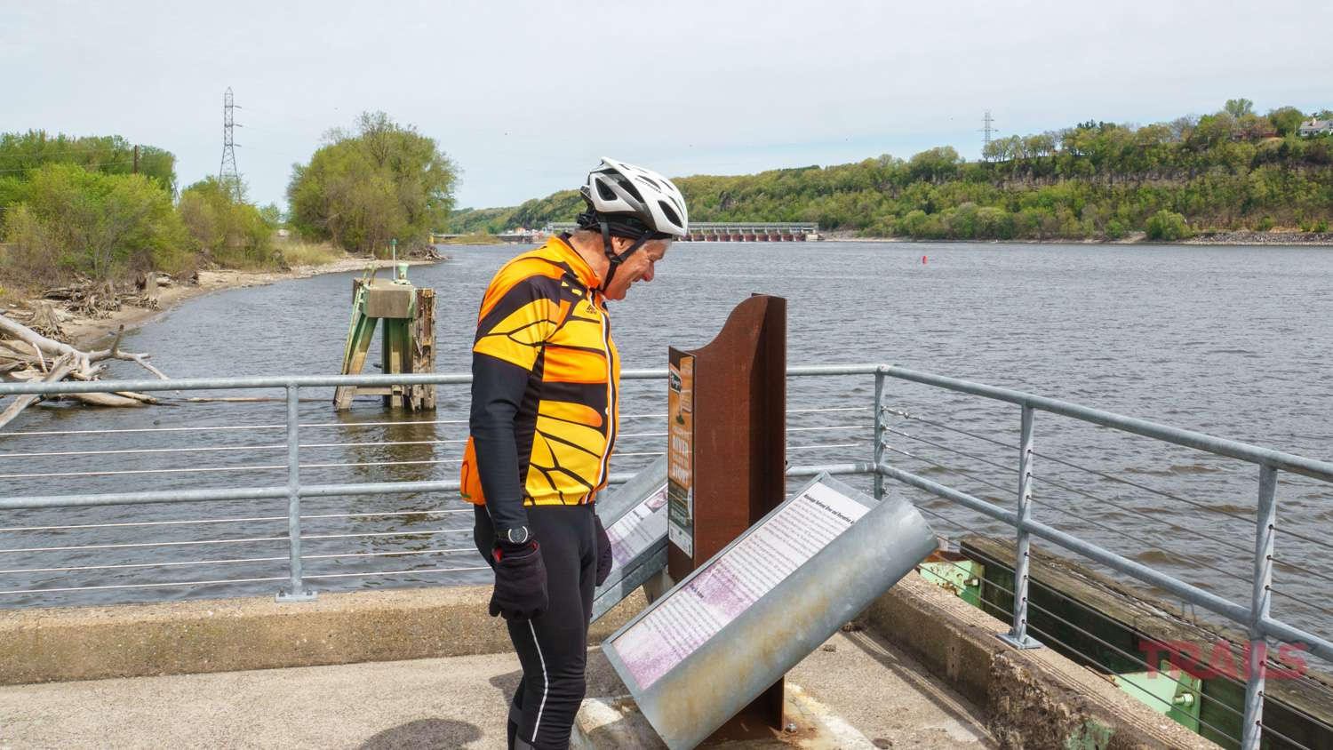 A man dressed in bicycle gear reads an interpretive sign on a fishing pier