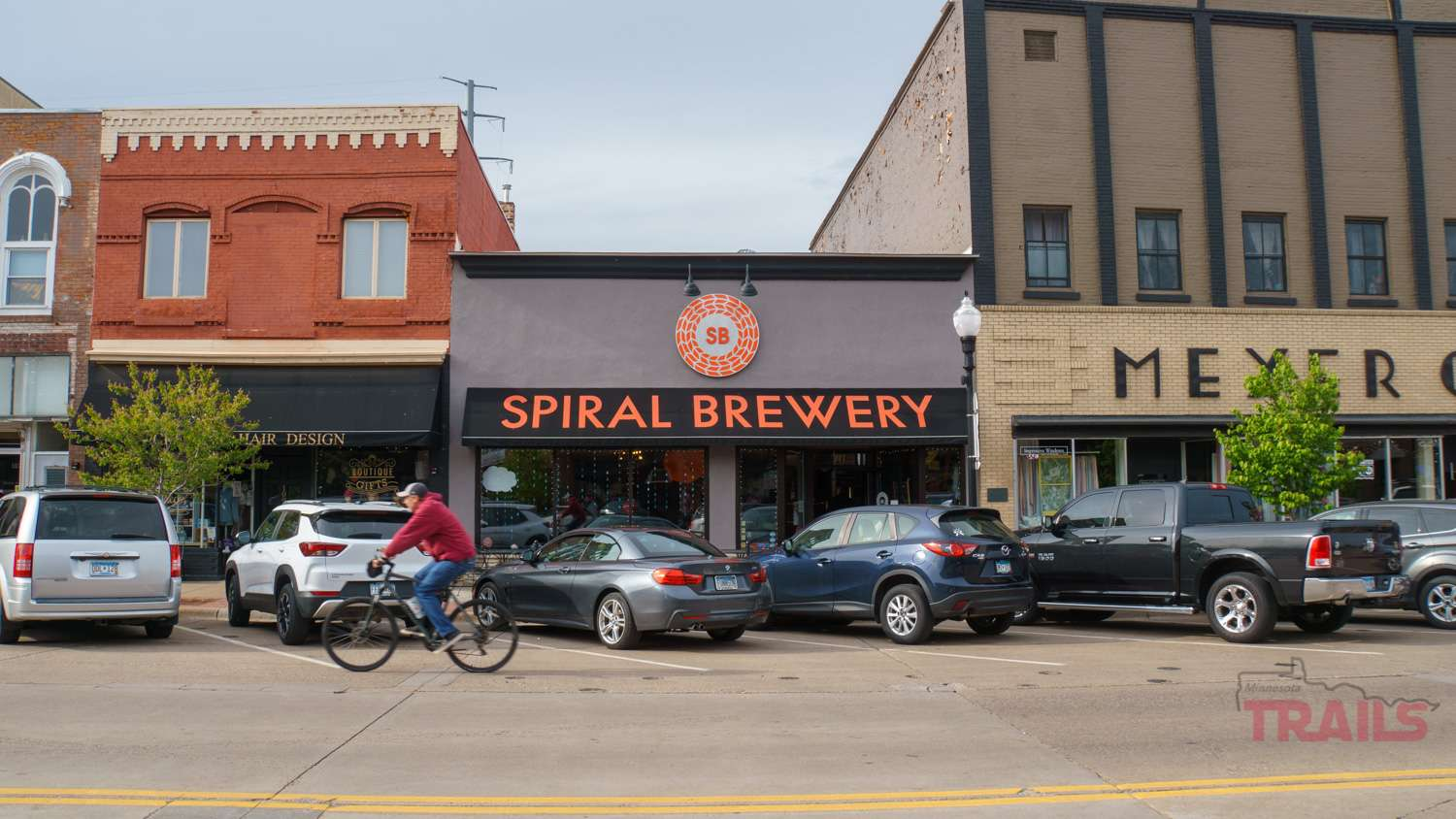 A man on a bike passes in front of Spiral Brewery in Hastings, MN