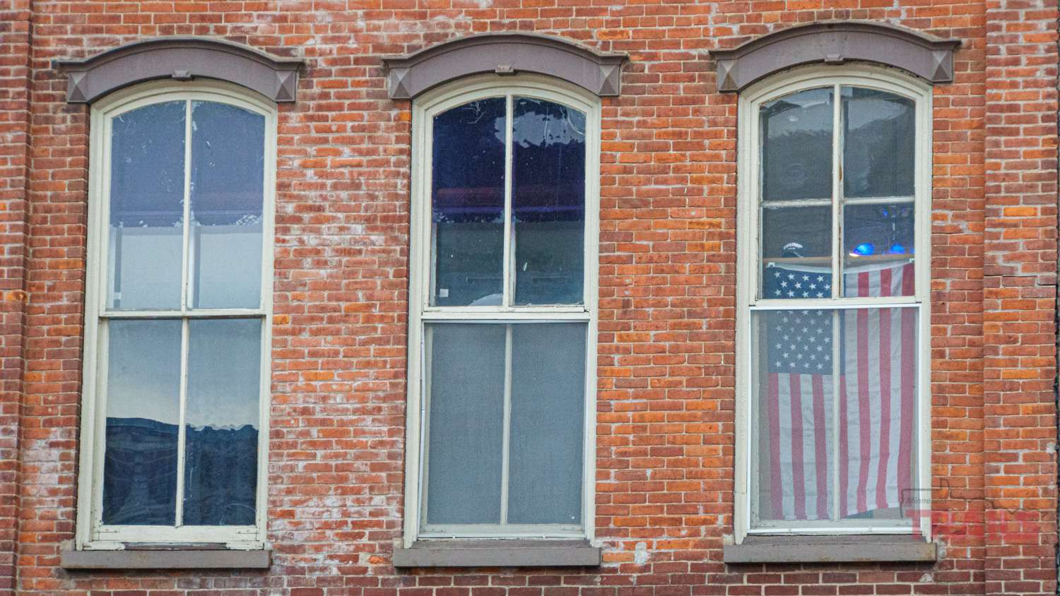 A window in an old brick house displays an American flag