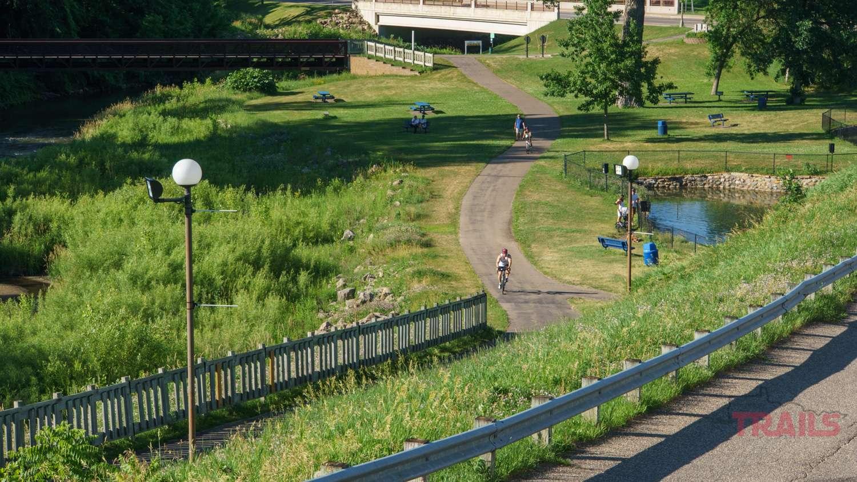A bicyclist rides through a park on a trail
