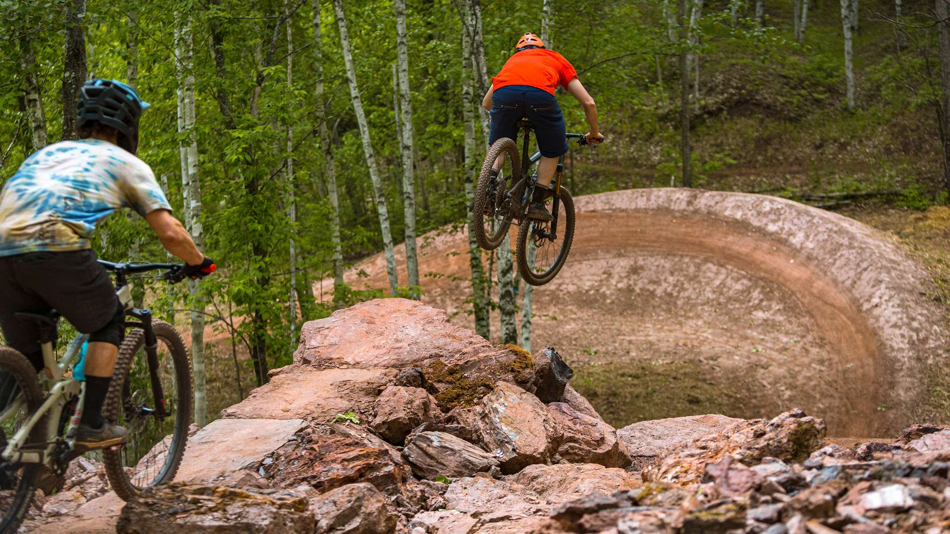 Mountain bikers ride a difficult and rocky trail