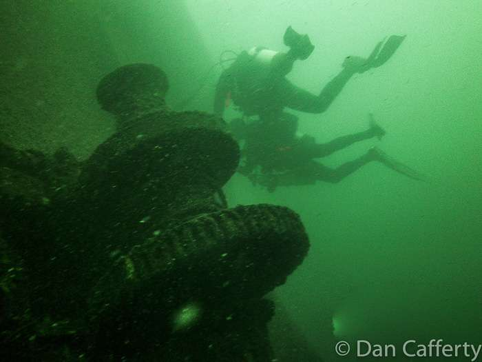 Two divers float above a piece of wrecked equipment underwater while diving the wreck of the Madeira