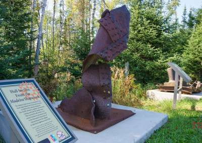 The rusted part of a shipwreck is displayed alongside an interpretive sign at Split Rock Lighthouse State Park