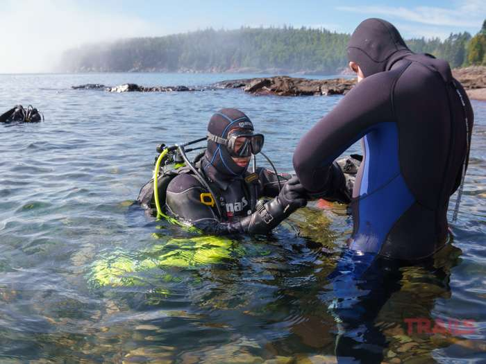 A man in a diving suit assist another man with donning his gloves at Split Rock Lighthouse State Park