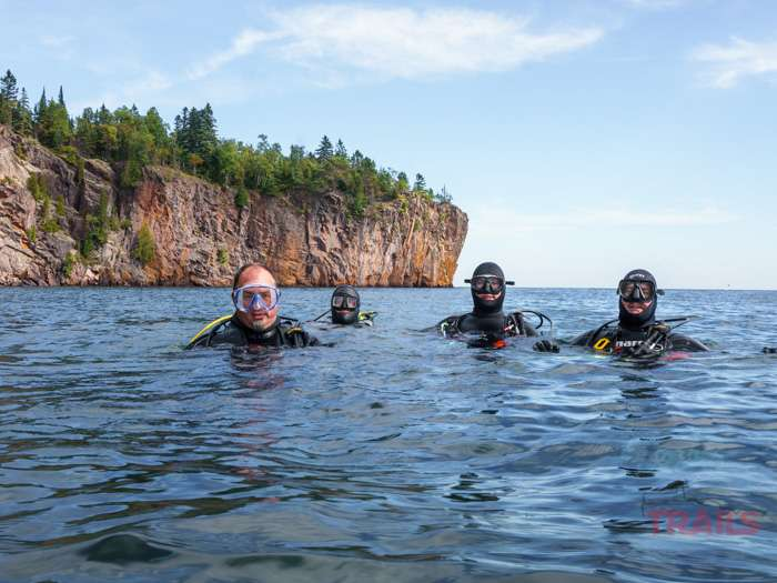 A group of divers pose for a group photo on the surface of Lake Superior at Split Rock Lighthouse State Park