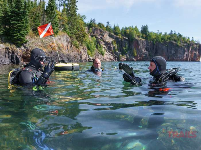 Two divers practice their hand signals while another one watches at Split Rock Lighthouse State Park