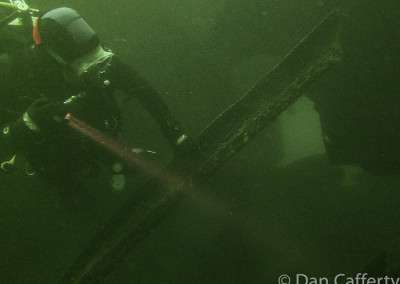 A diver shines a flashlight onto a rusted piece of metal underwater