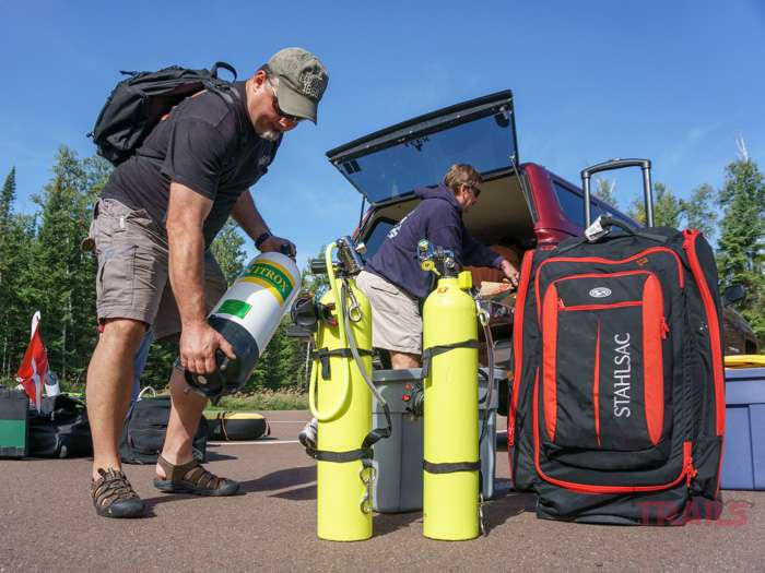 A man unloads a tank of Nitrox gas from the back of a pickup truck at Split Rock Lighthouse State Park