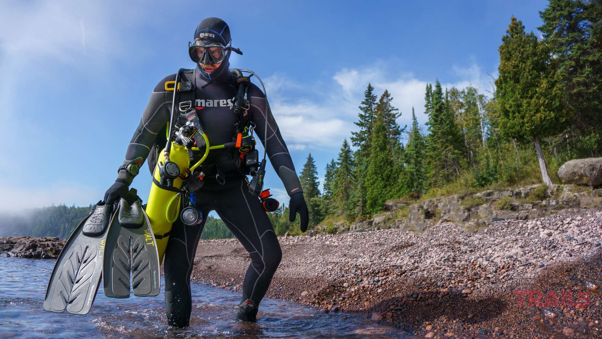 A man in a diving suit walks into the water carrying flippers