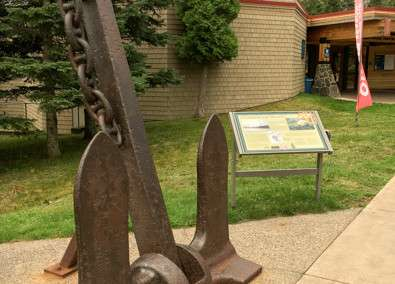 A large ship's anchor is displayed in front of a building at Split Rock Lighthouse State Park