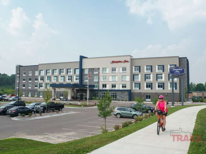 A woman rides her bike on a trail in front of a Hampton Inn Hotel