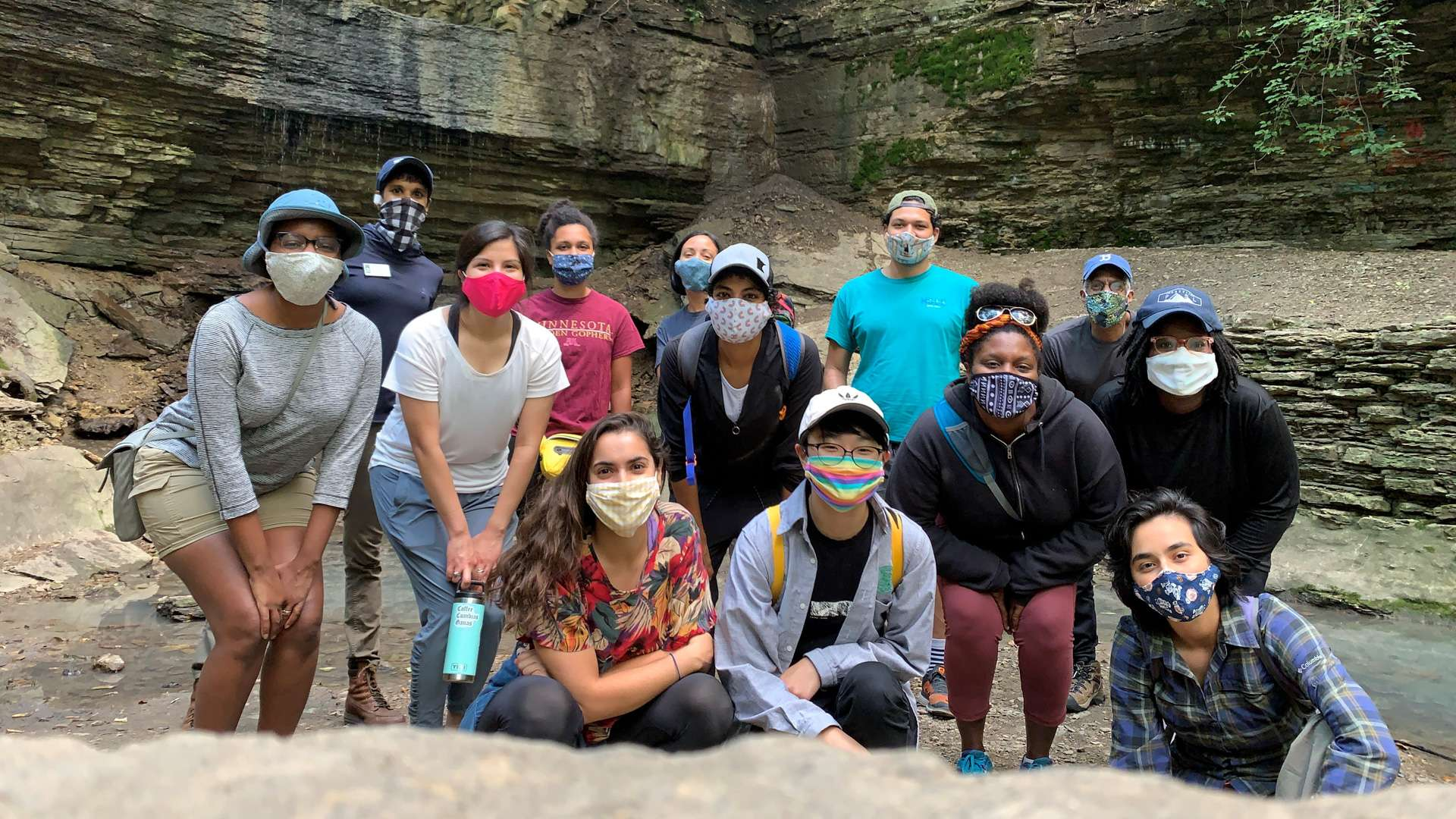 A group pf people wearing protective face masks are taking a break from hiking to gather for a group photo