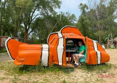 Two people sit inside an antique car painted to look like a clownfish at Hot Sam's Photo Park in Lakeville MN