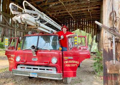 A man poses with an antique fire truck at Hot Sam's Photo Park in Lakeville MN