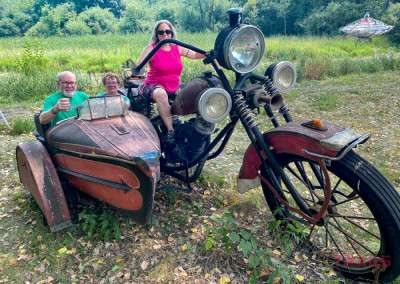 Three people pose on an oversized motorcycle sculpture
