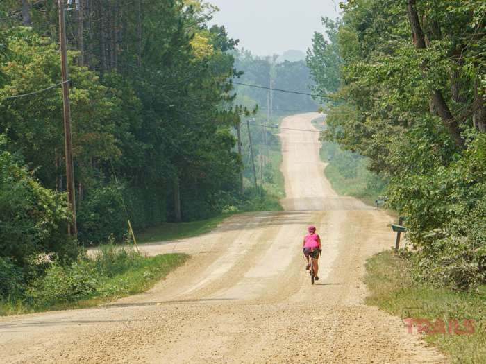 A woman rides her bike down a dusty gravel road