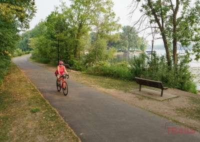 A woman rides a bike on a trail along a lake