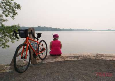A woman pauses at a scenic lake overlook while on a bike ride