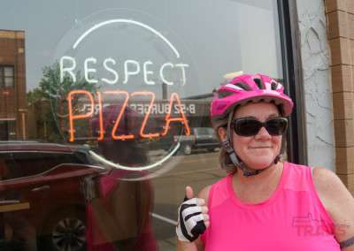 A woman poses in front of a neon sign that says Respect Pizza