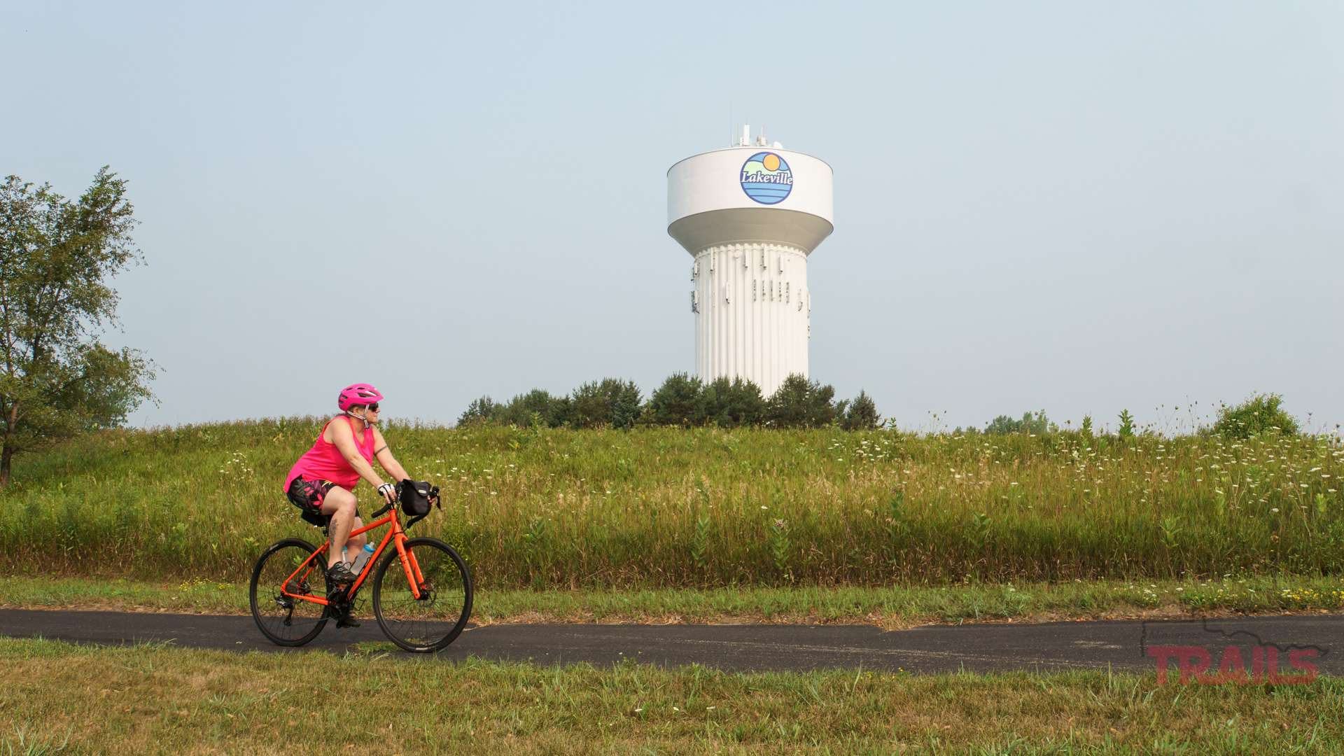 A woman rides a bike on a trail in front of a water tower in Lakeville MN