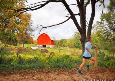 A man runs past a bright red barn on a leaf-covered trail on a cloudy day