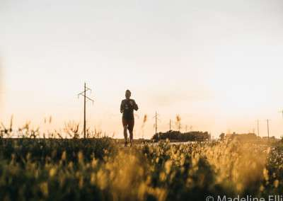 A man runs along a deserted gravel road by himself flanked by fields under overcast skies