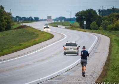 A man runs along the shoulder of a road by himself after a rain