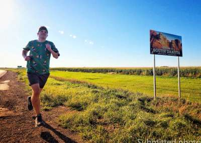 A man runs along a deserted road past a Welcome To South Dakota sign