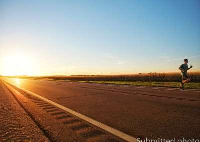A man runs along a deserted road by himself at dusk