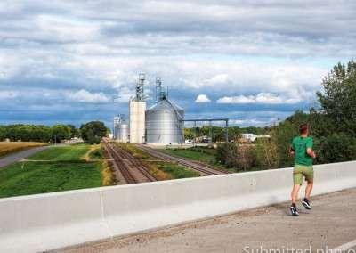 A man runs along a road, crossing a railroad bridge with grain elevators in the background