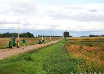 A man runs along the shoulder of a road and waves at a farmer driving a tractorA man runs along the shoulder of a road and waves at a farmer driving a tractor