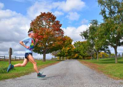 A man runs on a trail past colorful trees in the fall under partly cloudy skies