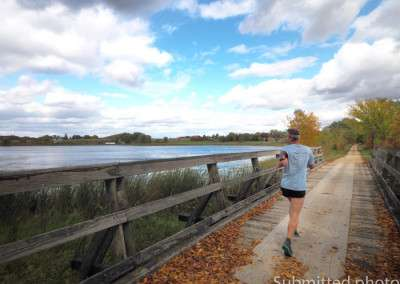 A man runs on a trail crossing a bridge over a lake in the fall under partly cloudy skies