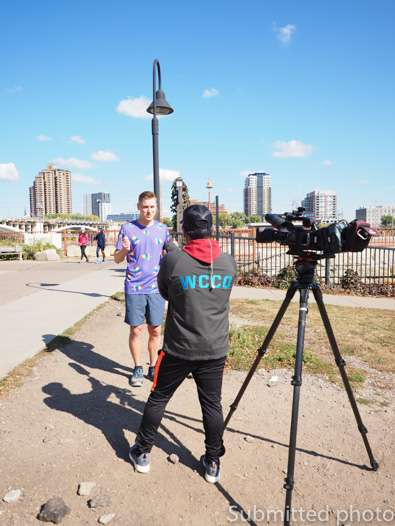 A man is being interviewed by a man with a TV camera in front of the Minneapolis skyline