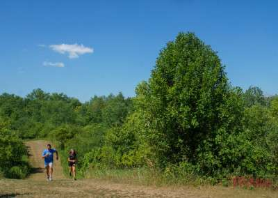 Two people run down a trail at Ritter Farm Park in Lakeville MN