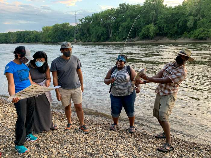 A group of people are gathered by a river bank trying to identify a fish via a chart