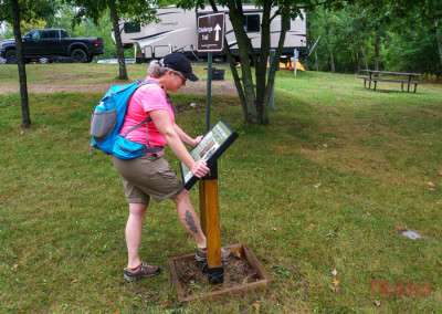 A woman uses a cleaning station to remove seeds of invasive plants from her boots