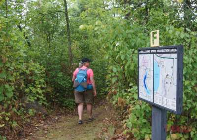 A sign depicting a map shows the right way on a hiking path