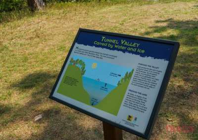 An interpretive sign shows how a lake was formed on a hiking path