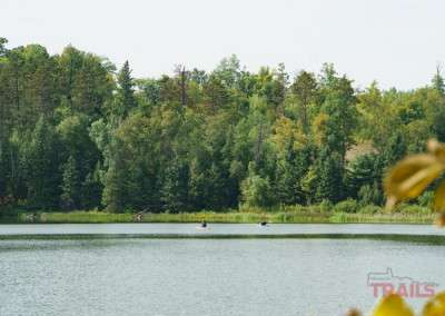 Three people explore a lake in kayaks on a calm day